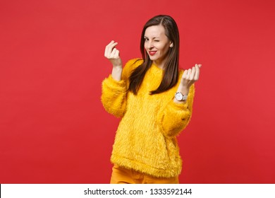 Tricky young woman in yellow fur sweater blinking, rubbing fingers, showing cash gesture, asking for money isolated on red background. People sincere emotions, lifestyle concept. Mock up copy space