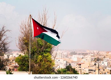 tricolor flag of Jordan on the background of the old poor of the city and blue sky