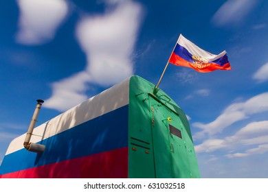 Tricolor vagon with chimney and russian flag against blue sky with clouds.