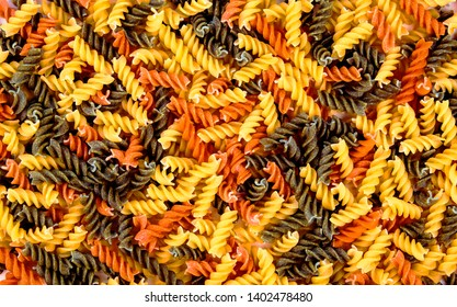 Tricolore fusilli Italian pasta - food background texture for design, and love of Italian cuisine, recipes and cooking.