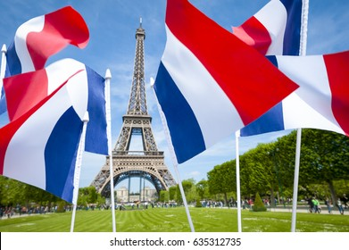 Tricolour French flags flying in front of a bright spring view of the Eiffel Tower in Paris, France
