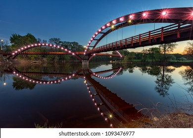 The Tridge at night, spans the confluence of the Chippewa and Tittabawassee Rivers in Chippewassee Park in Midland, Michigan. The bridge reflects in the still river waters below