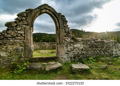 Tridomi, Czech Republic - October 29 2016: Stone ruins of the former medieval church of St Nicholas, svaty Mikulas, standing in the middle of the forest. View of the door. Sun over horizon.
