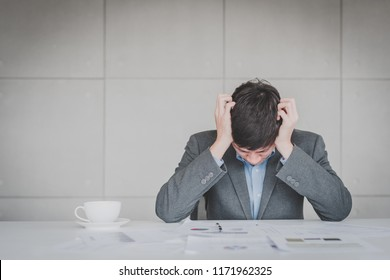 Tried Asian businessman feeling headache and stress from work in office