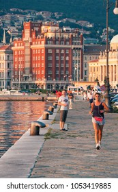 TRIESTE, ITALY. August 13, 2015: Wharf of Trieste seaport in northern Italy. Some people are walking and do some physical activity. Evening light, some buildings in the background and the mountain.