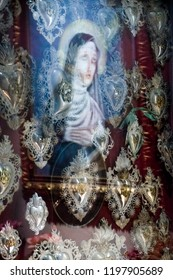 Trieste, Italy - August 27 2018: the image of Clare of Assisi is reflected in the glass that protects the ex-vows dedicated to her. Church of Santa Maria Maggiore