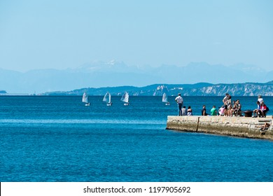 """Trieste, Italy - August 27 2018: Sailing boats of the rowing school off the """"Audace"""" pier"""