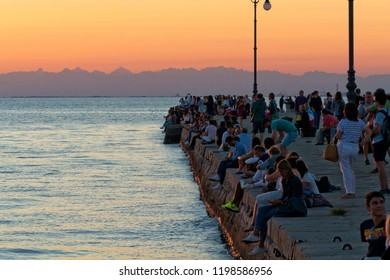 """Trieste, Italy - August 27 2018: Triestines and tourists gather all on the """"Audace"""" pier to enjoy the spectacle of the sunset over the Adriatic"""