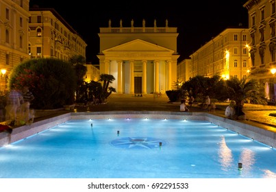 TRIESTE, Italy - August  3, 2017: Night view of Piazza Sant'Antonio Nuovo with the catholic church of Sant'Antonio Taumaturgo and the fountain in the foreground in Trieste, Italy