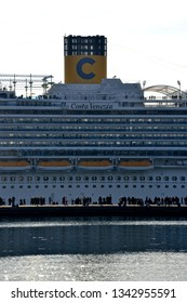Trieste, Italy - March 3, 2019 : Costa Venezia cruise ship moored at the cruise terminal of Trieste and a crowd looking at it on the pier Audace.