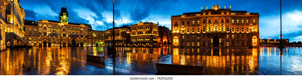 Trieste, Italy. Unity of Italy Square in Trieste, Italy at night during the heavy raining. Illuminated buildings - town hall and cloudy sky. People with umbrellas