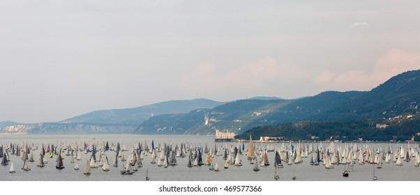 Trieste,Italy October 12,2014:Start of Barcolana 2014. Thousands of sails racing in the Adriatic sea during the Barcolana regatta. In background Miramar Castle.