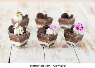 Trifle black and white chocolate with cookie. Decorated with a flower on old wooden white background. English traditional sweet dessert .
