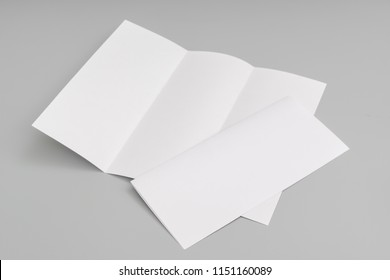 Trifold white template paper on blue background.