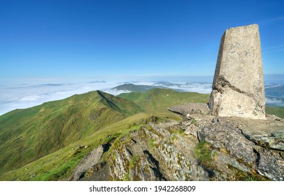 The trig point marker on the mountain summit of Ben Lawers looking out over the summit of Beinn Ghlas and Meall nan Tarmachan with a cloud Inversion covering Loch Tay in the Scottish Highlands, UK.