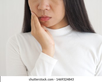 trigeminal neuralgia and temporomandibular joint and muscle disorder in asian woman, She use hand touching her cheek and symptoms fo pain and suffering on isoleted white background