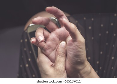 Trigger Finger is a defect in a tendon causing a finger to jerk or snap straight when the hand is extended. with retro filtered / Woman's hands ring finger