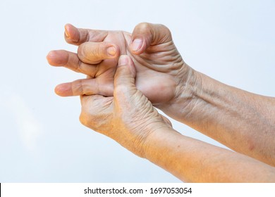 Trigger Finger lock on middle finger, Senior woman's left hand massaging her right hand Suffering from pain on white background, Close up shot, Office syndrome, Healthcare, Massage, Asian body concept