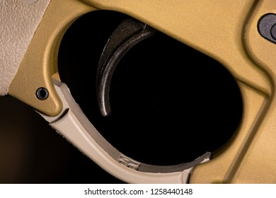 Trigger on an AR-15 in a gold color on a dark background