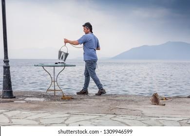 TRIKERI, GREECE - MAY 5, 2018: restaurant keeper preparing fish for dinner outdoors on the greek peninsula Pilion