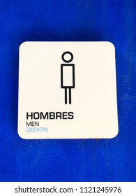Trilingual (Spanish, English and Nahuatl language) men's restroom sign attached to a blue wall.