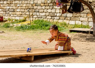 TRIMPHU, BHUTAN - MAR 8, 2017: Unidentified Ngalops little boy plays with a tiny motorcycle. Ngalops is one of the most populous ethnic groups of Bhutan