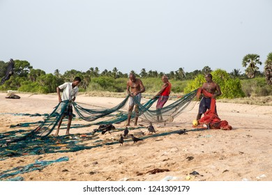 Trincomalee, Sri Lanka - August 20, 2018: Fishermen sorting a big fishing net at Nilaveli Beach