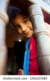TRINIDAD - CUBA / 03.10.2015: Little schoolgirl from Trinidad looking over wooden fence of the school, Trinidad, Cuba