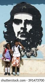 TRINIDAD - CUBA / 10.03.2015: Children from Trinidad City in front of Che Guevera graffiti