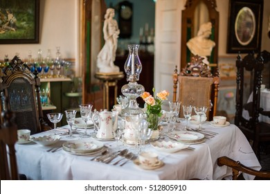 TRINIDAD, CUBA - APRIL 13, 2014: The served table with white cloth, porcelain plates, china, crystal glasses and vase. On a background marble statues and antique registration of the room at restaurant