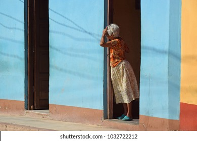 Trinidad, Cuba - April 27,2016: Elderly woman looks out of her house