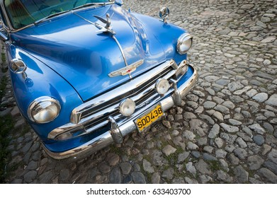TRINIDAD, CUBA - CIRCA MAY, 2011: Vintage blue American car stands parked on cobblestone street in the colonial center of the historic town.