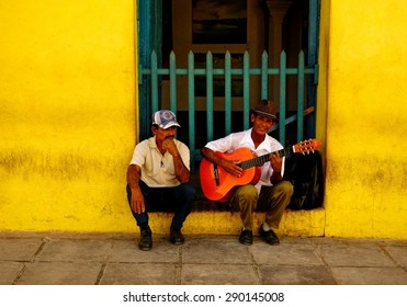 TRINIDAD, CUBA - DECEMBER 24, 2013: An unidentified street musician and another unidentified man sitting by the wall of an old yellow building in the historic part of Trinidad, Cuba on Christmas Eve.