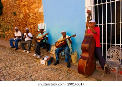 TRINIDAD, CUBA - DECEMBER 24, 2013: A group of unidentified musicians playing multiple instruments for the tourist in the cobble street in the historic part of Trinidad, Cuba on Christmas Eve 2013.