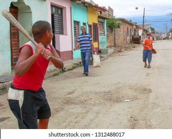 Trinidad, Cuba - January 16th, 2009: Two young boys play baseball on a dirt road in a neighbourhood backstreet with a man passing by with groceries