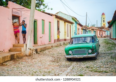 Trinidad, Cuba - June 12 2014:  People standing on the street and american oldtimer driving past them in Trinidad, Cuba