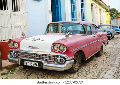 Trinidad, Cuba - June 12 2014:  American vintage car colored with red and white color parked in the narrow street of Trinidad, Cuba