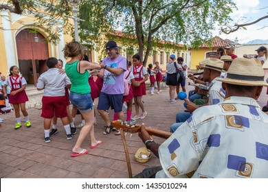 Trinidad, Cuba - June 6, 2019: People are dancing to the live music in the streets of a small Cuban Town during a vibrant sunny day.