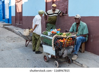 Trinidad / Cuba - March 15, 2016: There's a fruit and vegetable cart set on a corner. One Cuban man sits on an overturned box behind the cart, waiting for a shopper.