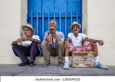 TRINIDAD, CUBA - MAY 4, 2017; Cuban men smoking sigars in front of a blue wooden door in Trinidad, Cuba
