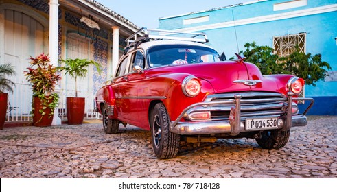 Trinidad, Cuba, Nov 28, 2017 - Red Classic 1950's Chevrolet is parked in front of a home