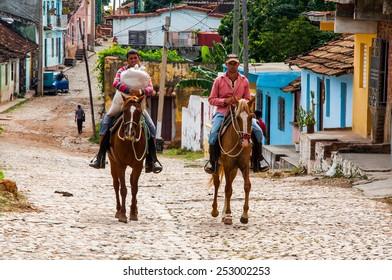 TRINIDAD, CUBA - NOVEMBER 18, 2013: Two Cuban men are riding horses in Trinidad, Cuba. Trinidad has been one of UNESCOs World Heritage sites since 1988.