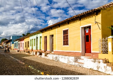 TRINIDAD, CUBA - NOVEMBER 21, 2017: View of Trinidad street with colorful (red, yellow, green, blue) houses, cobbled road and bars in windows. Trinidad is a UNESCO listed city and popular destination.