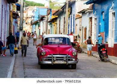 TRINIDAD, CUBA - NOVEMBER 22, 2017: Typical street scene with people, old cars and colorful buildings. Trinidad is a popular tourist destination and famous for its architecture and vintage style