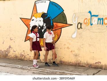TRINIDAD, CUBA - NOVEMBER 5, 2015: Cuban elementary school students  in uniform on city streets walking after classes