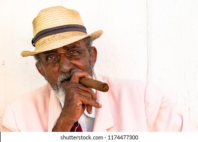 Trinidad, Cuba-August 6, 2018: Cuban man smoking a large cigar in the colonial village. He is busking for tips. Trinidad is a major tourist attraction and an Unesco World Heritage Site