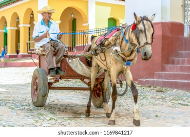 Trinidad, Cuba-July 9, 2018: Senior Cuban citizen with a horse-drawn carriage in Trinidad. Trinidad is a Unesco World Heritage Site and a major tourist attraction in the Caribbean Island