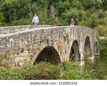 Trinidad de Arre, Navarre, Spain - September 4, 2014: Pilgrims on the medieval stone bridge over the River Ulzama