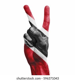 Trinidad and Tobago national flag painted onto a male hand showing a V peace sign
