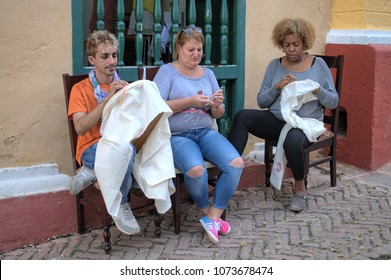 TRINIDAT, CUBA - January 8, 2018: Cuban artists handicraft embroidery fabrics for tourists on the street.